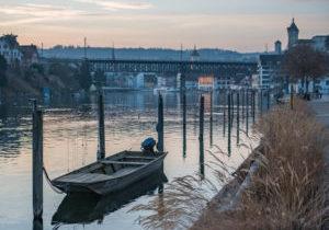 Ein Weidling auf dem Rhein, vor der Schaffhauser Altstadt bei Sonnenuntergang.